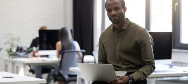 Homme d'affaires afro-américain souriant et heureux assis sur son bureau et tenant un ordinateur portable dans un bureau